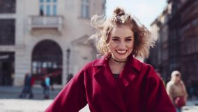 Close up view of a young playful woman walking down the street, turning to camera and laughing happily. Stylist outfit stock footage