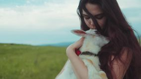 Close up view of a young pretty woman holding, kissing and petting white goat kid. Loving nature, cherish nature. Being. Happy, honesty. Beautiful landscape on stock video