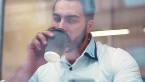 Close up view of a young stylish gentleman using his phone and drinking coffee. Close up view, camera stabilizer shot stock video