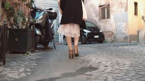 Close-up view of young stylish woman walking on cobblestone pavement road. Girl going through the street. Slow motion. Close-up view of young stylish woman stock footage