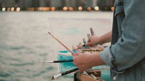 Close-up view of young woman holding the brushes and drawing the picture on shore of Michigan lake, Chicago, America stock video footage