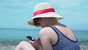 Close-up view of young woman using smartphone in hand at seashore abstract background stock footage