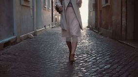 Close-up view of young woman walking at sunny spring city street in Europe. Stylish girl exploring the old town alone. Close-up view of young woman walking at stock video footage