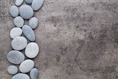 Spa flowers and massage stone, on grey background. Stock Photos