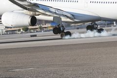 Commercial Airliner Landing On A Runway. Close up views of passenger jets touching down on a runway Stock Images