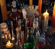 Close up of vintage bottles, flask and candles in alchemy laboratory. Old pharmacy, esoteric or alternative medicine concept. Black magic and occult objects Stock Photos