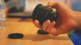 Close up vintage camera lens in the hands. On the table Stock Image