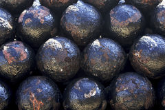 Close up of vintage cannonballs. Macro image of stacked weathered cannonballs Stock Photography