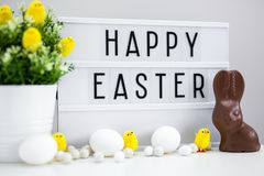 Close up of vintage lightbox with happy Easter greetings, chocolate bunny, Easter eggs and decorations. On the table royalty free stock photo