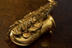 Close up of vintage saxophone. Golden saxophone on a wooden background Royalty Free Stock Image