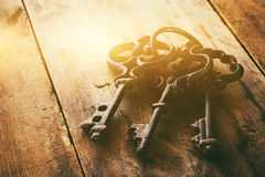 Close up of vintage skeleton keys over wooden table Royalty Free Stock Image