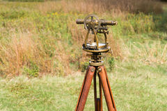 Close up of Vintage Surveyors Level (Transit, Theodolite) with wooden Tripod in a field. Royalty Free Stock Image