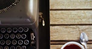 Vintage typewriter and black coffee on wooden table 4k. Close-up of vintage typewriter and black coffee on wooden table 4k stock video footage