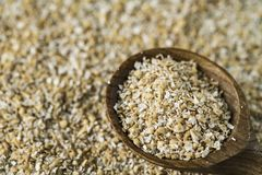 Heap oat bran with wooden spoon royalty free stock images