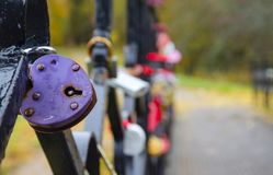 Close-up of violet heart-shaped padlock covered by drops of water in rainy autumn day. stock images