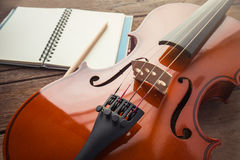 Close up of violin and book on wooden table Stock Image