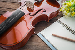 Close up of violin and book on wooden table Stock Photo