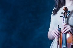 Concept for music news. Copy space. Smoky background. Close-up. Violin and bow in female hands. royalty free stock photo