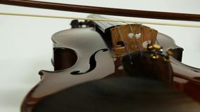 Close up violin and bow on white background. View from the side of violinist. stock footage