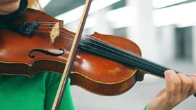 Close up of a violin in the female hands playing it. 4K stock video footage