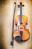 Close up of violin with a fiddlestick. On a wooden background Stock Photo