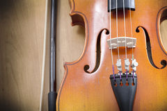 Close up of violin with a fiddlestick. On a wooden background Royalty Free Stock Image