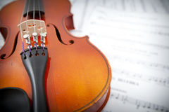 Close up of violin on the left with blurred music Royalty Free Stock Photo