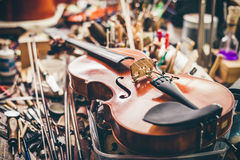 Close up of violin, luthier workshop in background Royalty Free Stock Photos
