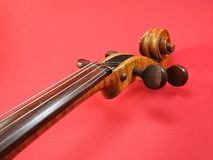 Close-up of a violin: scroll, peg-box and tuning pegs. Close-up of a violin: we can see the scroll, the peg-box, the tuning pegs and a piece of the neck with stock photo