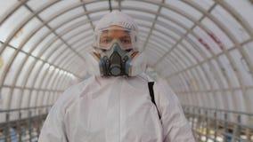 Virologist in protective hazmat, goggles and respirator walking