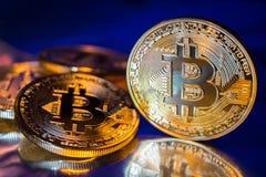 Close-up virtual novo dourado do dinheiro de Bitcoins da foto em um fundo azul Fotos de Stock