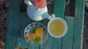 close-up, vista superior A mão da mulher toma um copo da posição do chá verde e do doce de fruta no banco video estoque