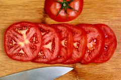 A Close up vivid image of tomato slices on a bamboo cutting board stock photos