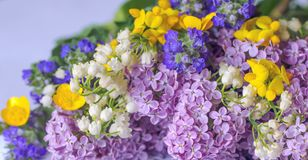 A close up voew of bouquet of blossom lilies and wild flowers with green leaves in the background stock images