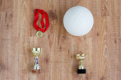 Close up of volleyball ball, cups and medals Royalty Free Stock Image