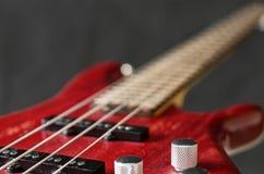 Close-up volume control of bass guitar. Close-up volume control of red bass guitar on gray background Stock Photo