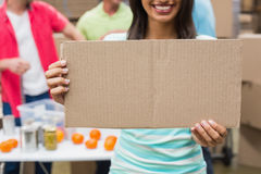 Close up of volunteer showing a poster. In a large warehouse Royalty Free Stock Photos