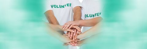 Close up of volunteer team putting hands together and blurry teal framing. Digital composite of Close up of volunteer team putting hands together and blurry teal Stock Image