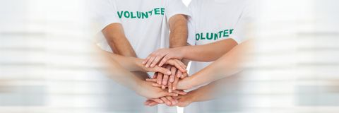 Close up of volunteer team putting hands together and blurry white framing. Digital composite of Close up of volunteer team putting hands together and blurry Royalty Free Stock Image