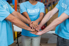 Close up of volunteers joining hands stock photo