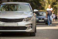 Close-up vooraanzicht van grijze zilveren die auto op stil gebied bij de vage bouw en groene bomenachtergrond wordt geparkeerd op royalty-vrije stock foto's