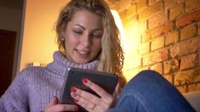 Close-up voorspruit van het volwassen Kaukasische blonde vrouwelijke texting op de camera bekijken en tablet die cheerfully gliml stock footage