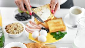 Close-up vrouwelijke hand het uitspreiden boter op gebraden broodtoost die mes gebruiken die ontbijt van voedsel genieten stock videobeelden
