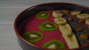 Close-up, Vrouwelijke Hand Uitgespreide Kiwi en Framboos op Fruit Smoothie stock footage