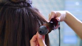 Close-up vrouwelijke handen die krullend ijzer gebruiken die krullen op lang donker haar maken stock footage