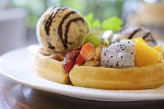 Close up waffles served with mixed fruits, sliced banana, ice-cream and topped with chocolate Sauce royalty free stock photos