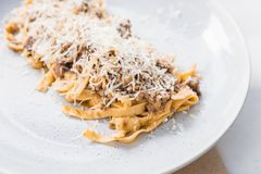 Close up Wagyu Ragu with Tagliatelle pasta topping with cheddar cheese.  Stock Photography