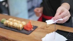 Close-up - the waiter put the sushi on board on the table in restaurant Royalty Free Stock Photos