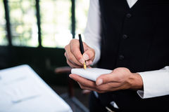 Close-up of waiter taking an order wearing a waistcoat. In a restaurant Stock Photo