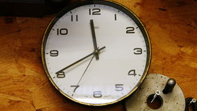 Close-up of wall clock on a table. In workshop stock footage